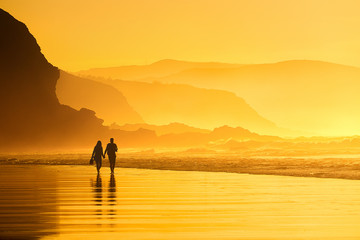 couple walking in the beach at the sunset