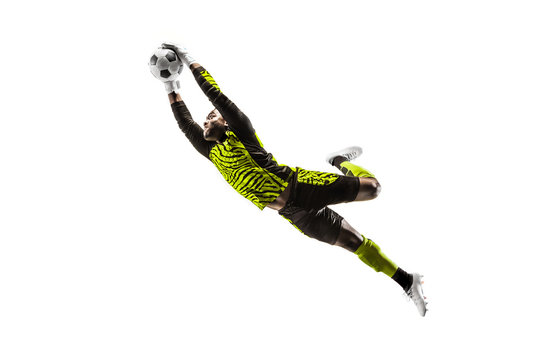 Male soccer player goalkeeper catching ball in jump. Silhouette of fit man with ball isolated on white studio background