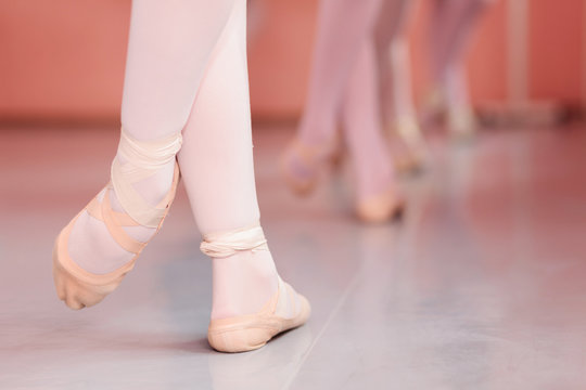 Close-up of teenage ballerina's feet, practicing ballet moves in a dancing studio. Low angle view, unrecognizable people