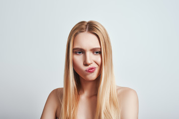 Hm...I do not know what to do. CLose-up portrait of young blonde woman folding lips and thinking what to do