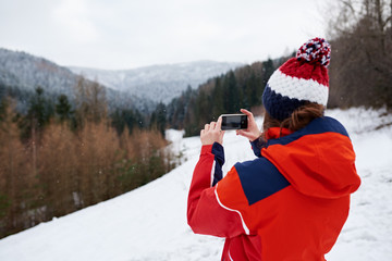 Fototapete - Young woman taking pictures while out for a winter hike