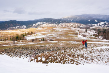 Fototapete - Young couple walking through a snow covered field in winter