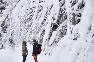 Fototapete - Young couple talking while hiking in a snow covered forest