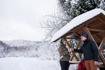 Fototapete - Young couple sharing coffee while out for a winter hike