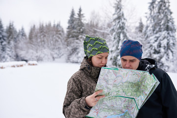Fototapete - Young couple reading a map while hiking in winter