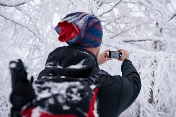 Fototapete - Hiker taking photos of a snow covered forest in winter