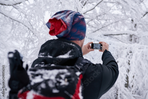 Fototapete Hiker taking photos of a snow covered forest in winter