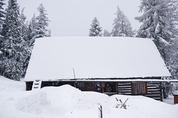 Fototapete - Couple standing on the porch of a snow covered chalet