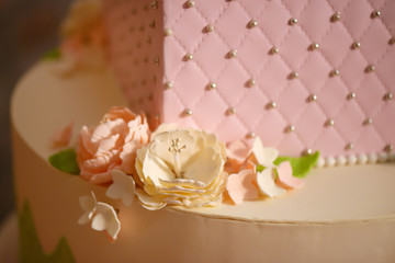 Close up of delicate icing floral decoration on a tiered cake, embellished with velvet pastel pink icing, sugar flowers and silver edible jewelry and beads, ready for a wedding or a birthday  party