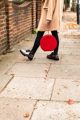 Unrecognisable stylish woman standing outdoors and holding round red velvet purse.