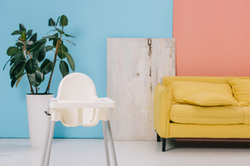 room with yellow sofa, highchair and large ficus in flower pot