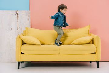cute little boy in blue jacket and green jeans jumping on yellow sofa