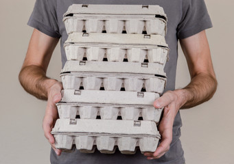 Caucasian man with gray t-shirt holding four cardboard egg boxes full of chicken eggs