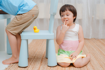 Sister puts a rubber duck on a chair under her brother's ass and hides on fool's day. Children's humor on April 1. Jokes and fun. Kids 3 years and 6 years