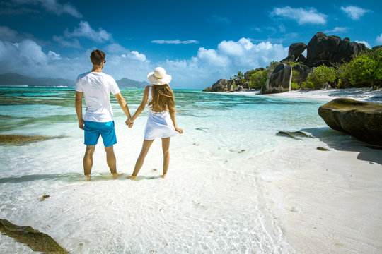 A young couple standing in shallow water on La Digue island, Seychelles