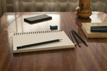 Notebook with drawings and pencil on wooden table.