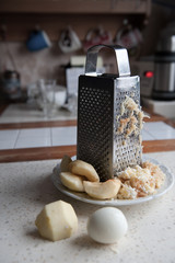 grater on the kitchen with egg