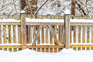 Wooden fence gate locked covered in white snow after heavy snowing snowstorm storm by house home with forest trees bushes in background in Virginia