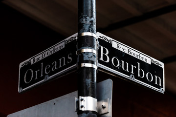 Orleans and Bourbon Streets Sign intersection text in New Orleans on lamp pole post at night isolated closeup