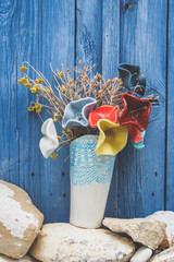 multicolored ceramic flowers are on a wooden blue background