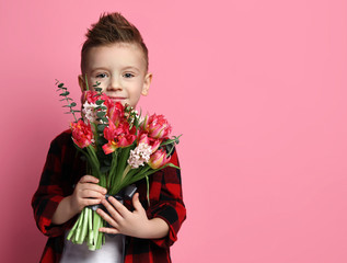 Nice little boy kid in red shirt with a big bouquet of spring flowers ready to congratulate with a Mothers day or other holiday