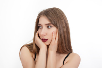 Portrait of a young beautiful girl with make-up isolated on white background. A woman looks away and holds her hands over her face.
