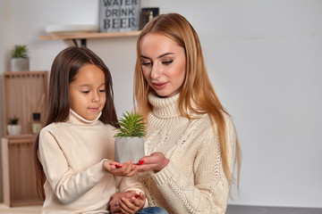 Beautiful mom and her small little daughter on weekend, sitting on countertop, consider a flower in a pot in light kitchen