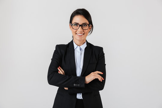Portrait of successful businesswoman 30s in formal wear and eyeglasses standing in the office, isolated over white background