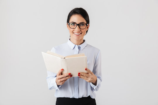 Photo of smiling female worker wearing eyeglasses reading book in the office, isolated over white background