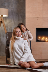 Mom with little girl relaxing on floor near a cozy sofa, Christmas lights in the fireplace