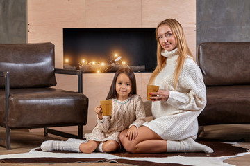 Young beautiful blonde woman hugs her little daughter on the couch with mugs of warm drink. Mother care about the child at home.