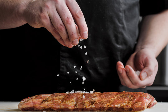 Raw piece of meat, beef ribs. The hand of a male chef puts salt and spices on a dark background.
