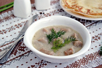 Machanka, thick sauce on meat broth with homemade pork sausages in a white bowl. Served with thin wheat pancakes. Belarusian cuisine
