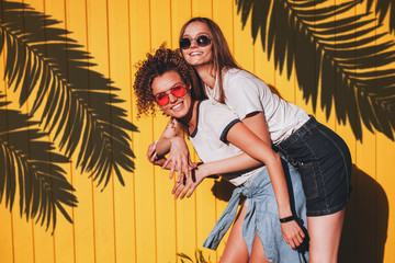 Candid shot of two lovely hipster women in glasses and denim clothes standing under the shadow of palm branches on a sunny summer day.