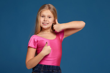 Portrait of adorable emotional little girl on blue background