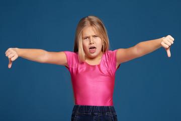 Portrait of emotional expressive little girl on blue background