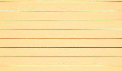 A simple background of bright yellow exterior siding on a house.