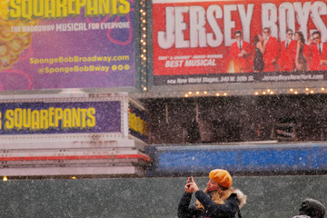 A woman takes photographs as snow falls in the Times Square neighborhood of New York