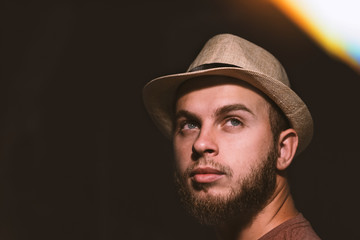 portrait of young man with a hat hippie hipster look face model concept idea strong eyes barb night photography