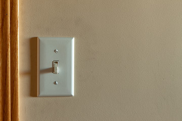 An old North American light switch on a wall near a doorway