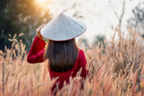Wall mural Asian woman wearing Vietnam culture traditional in african fountain flower field.