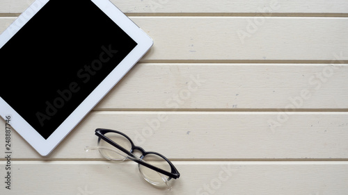 Wall mural taplet topview copyspace with glasses on wood background