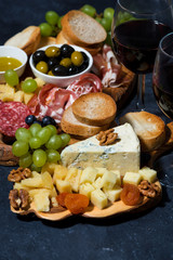 cheese platter on a wooden board, bread, fruit and cold cuts, vertical