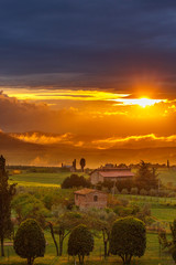 Sunset over a farm in a rolling Tuscan landscape in Italy