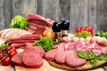 Fresh raw meat background with vegetables on wooden desk isolated on white background