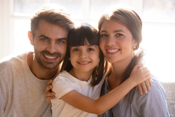 Happy mom dad and little daughter with smiling faces portrait