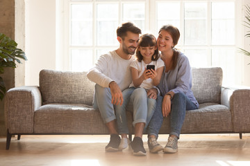 Happy family and kid having fun with smartphone at home
