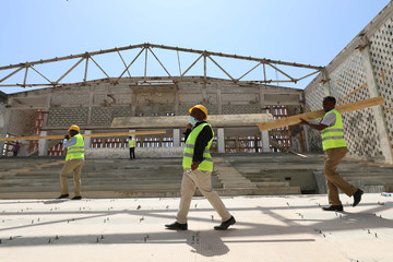 Construction workers carry wooden beams as they take part in the renovation project of Somalia's National Theatre in Mogadishu