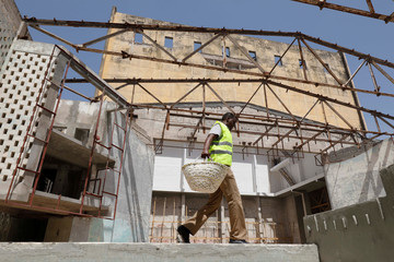 A construction worker walks on stage as he takes part in the renovation project of Somalia's National Theatre in Mogadishu