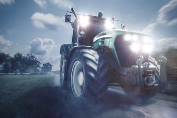 Fotoväggar - Traktor fährt auf einem Feldweg bei Nacht